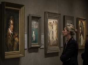 woman looking at Paintings hanging on wall